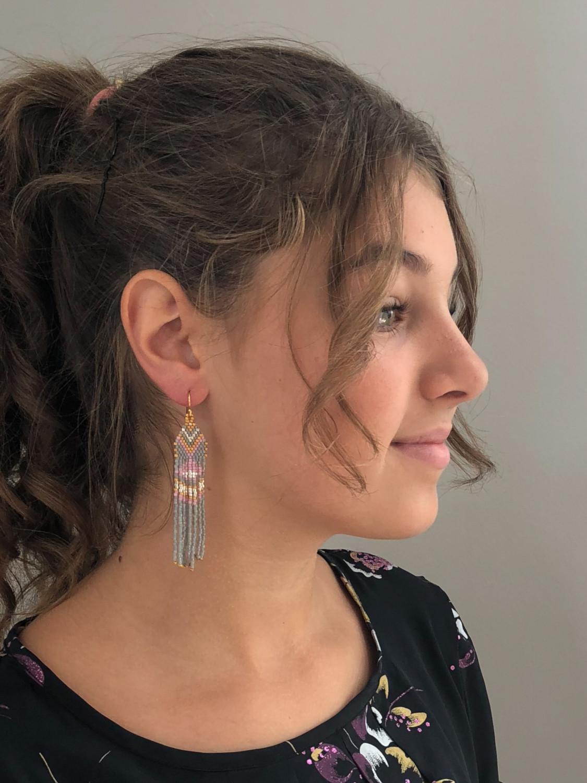 Model med lange boho øreringe i grå