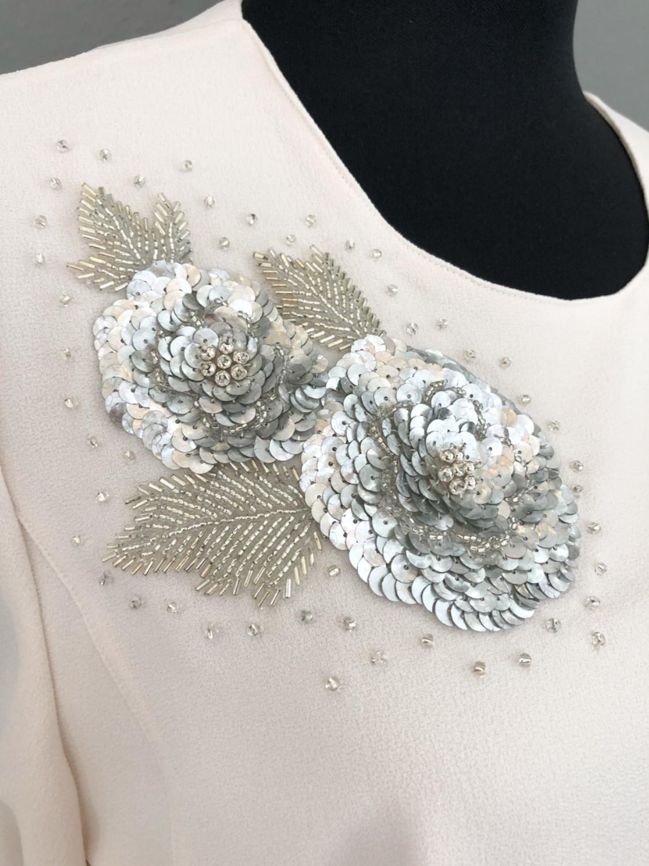 Cremefarvet bluse med skød og pailletmotiv - detalje