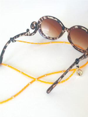 Brillesnor i orange med guld cowrie shell her vist på solbriller